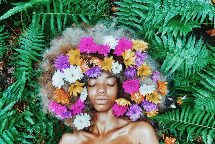 black woman with flowers in hair vsco in grass in peace